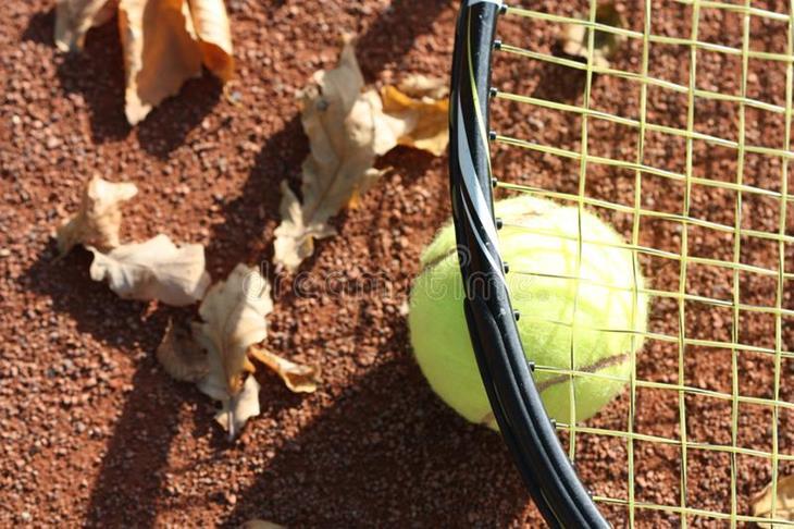 tennisbal-op-de-hof-en-herfstbladeren-129728633.jpg