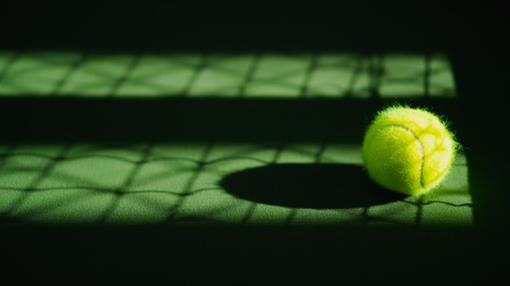 een-nieuwe-tennisbal-en-netto-schaduw-op-groen-hardcourt-met-licht-van-rechts_34939-458.jpg